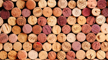 Closeup of a wall of used wine corks. A random selection of use wine corks, some with vintage years. Horizontal format that fills the frame.